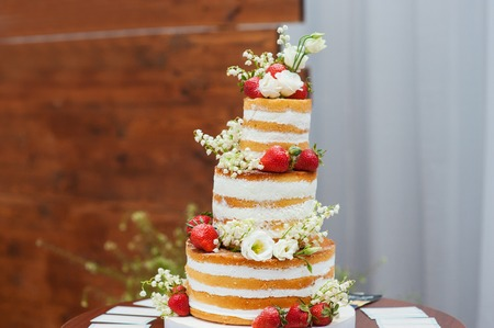 57590792 - three-tiered wedding cake with strawberries on table.